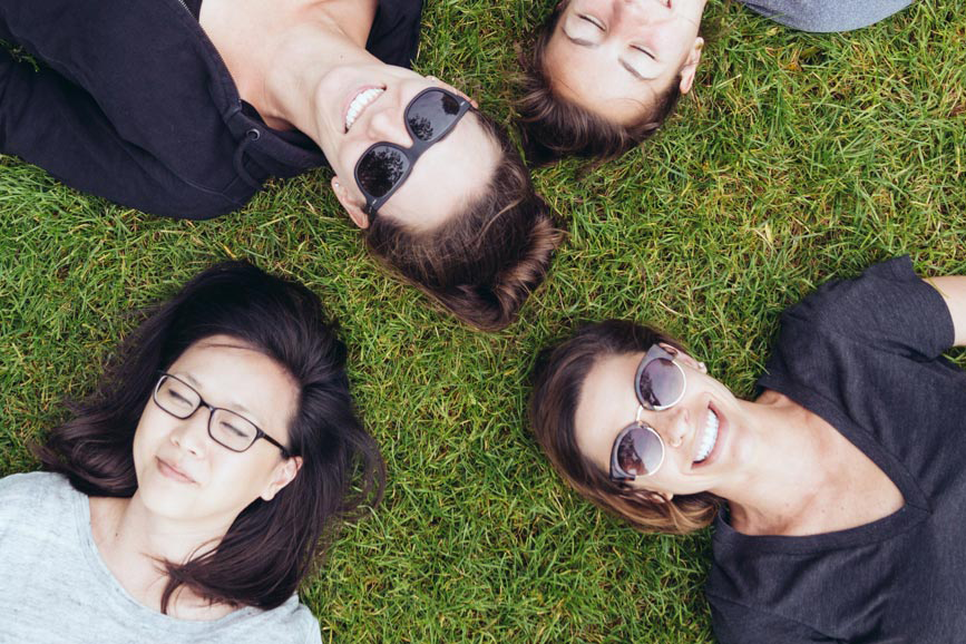 5 girls laying in grass