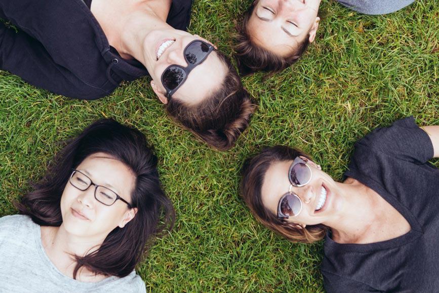 5 girls laying in grass